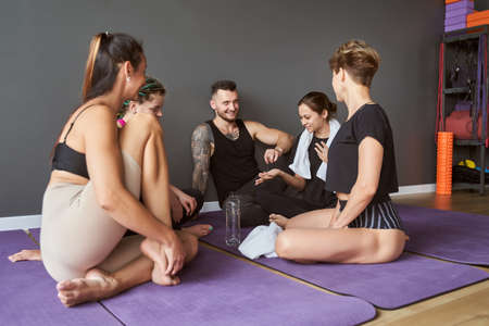 Yoga instructor talking to sport group while spending time in studio Archivio Fotografico