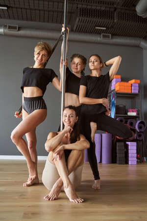 Slim females standing and sitting at the pylon in fitness class Archivio Fotografico