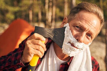 Cheerful guy shaving beard with axe in nature