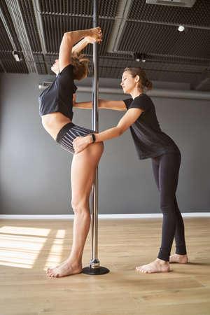 Beautiful slim women with pylon in fitness class Archivio Fotografico
