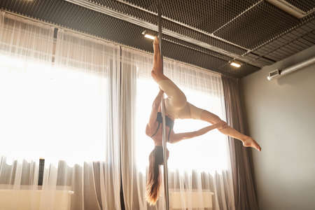 Young going up on a pole during her pole fitness class Archivio Fotografico