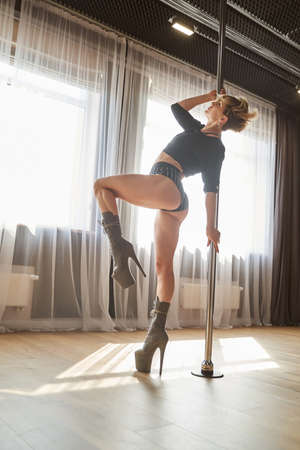 Good looking female pole dancer in black dance suit doing acrobatic element at the pole