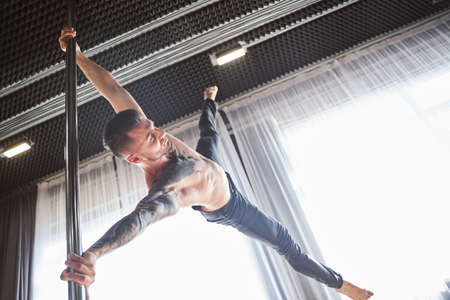 Shirtless muscular male pole dancer in action Archivio Fotografico