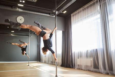 Female athlete is training on the pylon