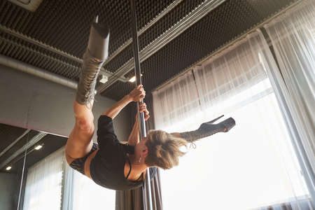 Attractive sexy woman pole dancer performing element in fitness studio