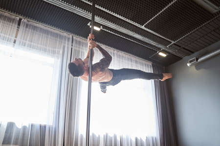 Young strong pole dancer man in black pants on pylon Archivio Fotografico