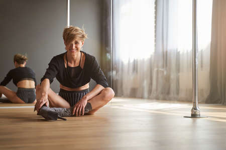 Happy smiling woman in black dance suit spending time in modern dance studio
