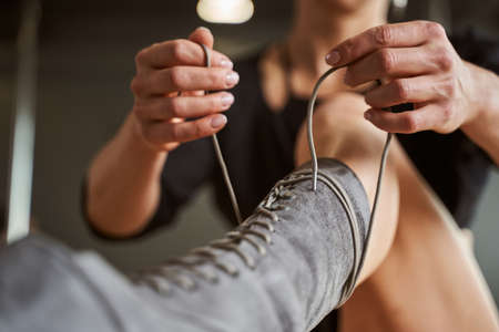Woman hand tying shoes in fitness class