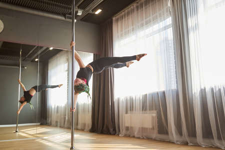 Sporty woman doing hard element of pole dance in fitness class Archivio Fotografico