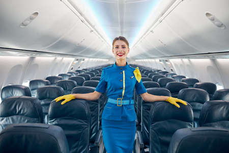 Beautiful air hostess posing at the photo camera in aisle of empty commercial airplane