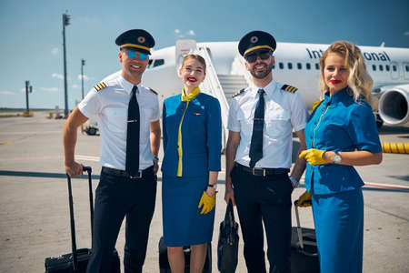 Cheerful airline workers standing in airfield before the flight
