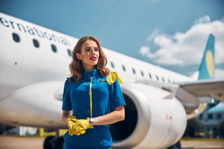 Beautiful young stewardess standing outdoors at airport