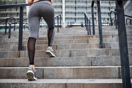 Athletic slim female running to urban stadium