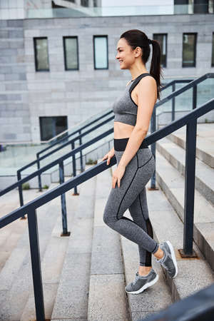 Merry athletic female doing workout in city centre