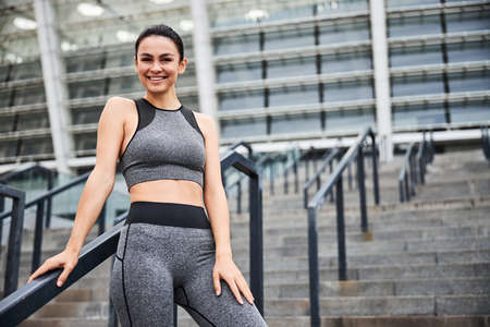 Smiling slim woman going training in city centre