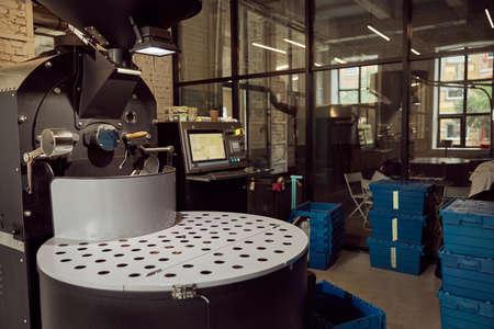 Coffee roasting machine and plastic crates at factory Archivio Fotografico