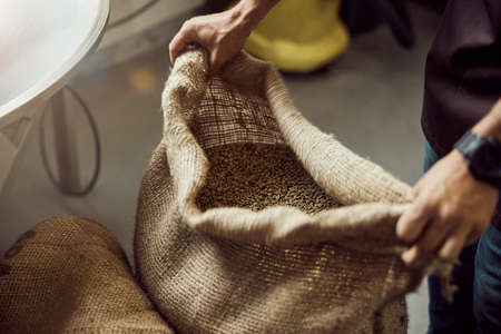 Male worker holding burlap sack with coffee beans