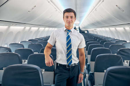 Young man standing in the empty board of commercial airplane