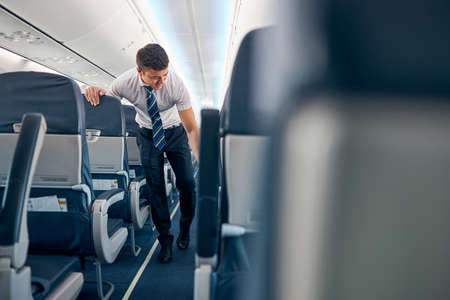 Confident male working on the empty salon of passenger airplane 免版税图像