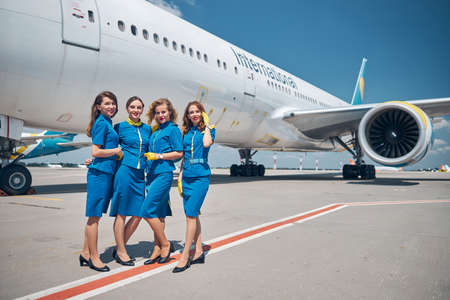 Group of beautiful stewardesses standing outdoors in airfield Banque d'images