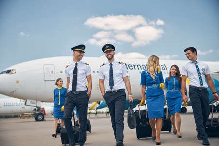 Cheerful airline workers with travel suitcases walking down the airfield