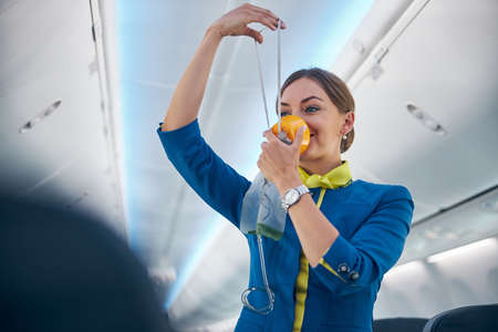 Air hostess showing how to use an oxygen mask on board