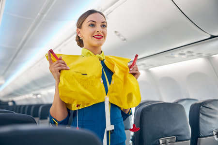 Flight attendant on board an airplane holding life jacket before flight procedure
