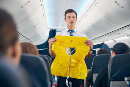 Steward demonstrating airplane rules for safety on board