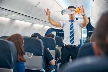 Steward demonstrating safety procedure prior to commercial airline flight took off