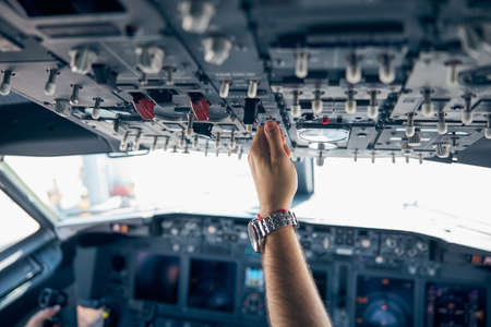 Pilot hand pushing on the dashboard in the aircraft Imagens