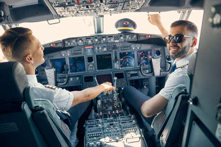 Two handsome male sitting in the cabin of aircraft Reklamní fotografie