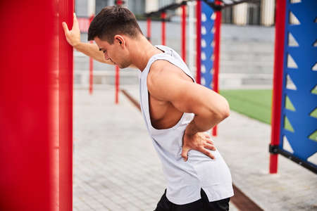 Athletic young man exhausted after training on sports ground Stock Photo