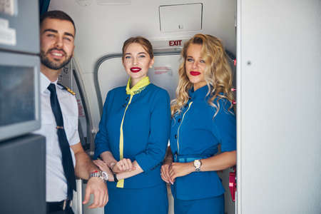 Beautiful air hostess with captain on the board of aircraft