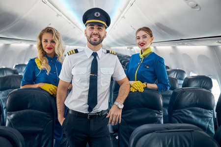 Happy smiling handsome pilot with two air hostess on the board of plane