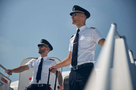 Confident males wearing sunglasses with rolling bags looking down on the moving ramp