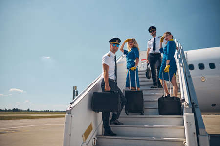 Beautiful female stewardesses with two handsome pilots looking and posing at the photo camera in the outdoors Stock fotó