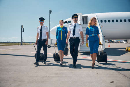 Two charming stewardesses with beaming captain and second pilot in front of commercial airplane