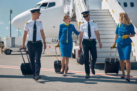 Happy friendly team of pilots and stewardesses wearing uniform going to the airport with rolling bags Stock fotó