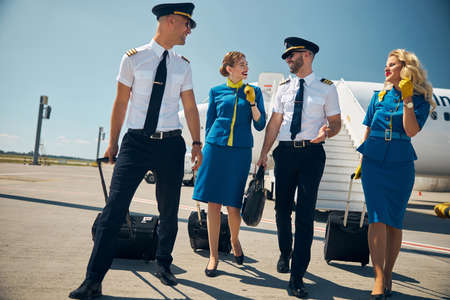 Young attractive team of stewardesses with confident men going to the international airport after flight Stock fotó