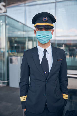 Handsome male pilot in medical mask standing on the street