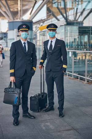 Handsome young pilots in protective face masks holding travel bags and looking at camera while waiting for flight at airport Imagens