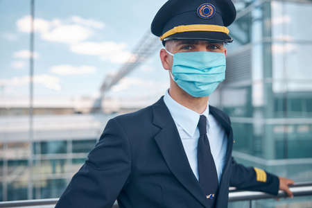 Male pilot in medical mask standing in airport terminal