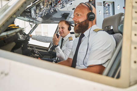 Two experienced pilots navigating the plane from cockpit 写真素材
