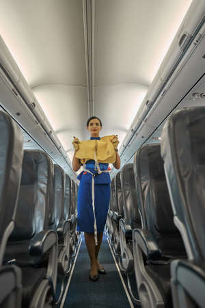 Professional flight attendant standing in the cabin with life vest