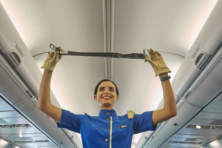 Enthusiastic stewardess demonstrating the seat belt in the plane