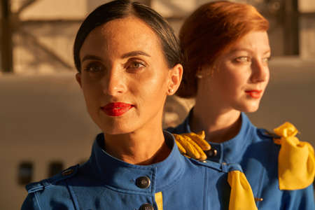 Smiling beautiful stewardesses in the evening sunlight