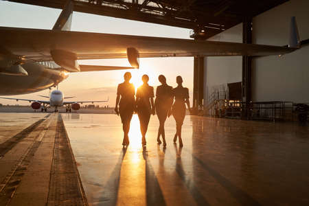 Unidentifiable stewardesses in the sunset light in hangar