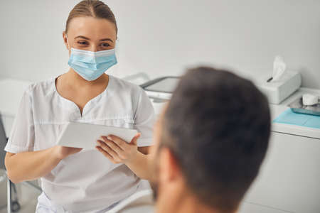 Charming esthetician with tablet computer talking with male patient