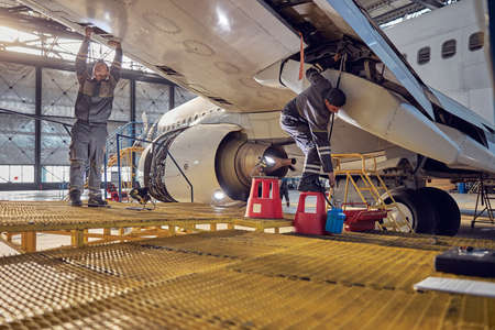 Technical aviation specialists fixing flight control surfaces Stock Photo