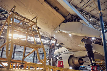 Men mechanics repairing of wing and engine of the aircraft in the hangar